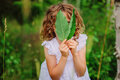 Child girl hiding behind green leaves in summer forest