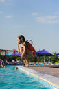 Child girl jumping into swimming pool Royalty Free Stock Photo