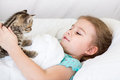 Child girl with kitten in the bed laying Royalty Free Stock Photography