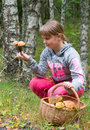 Child girl with a lot of mushrooms in basket Stock Images