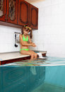 Child girl make mess, flooded kitchen imitating swimming pool, f Royalty Free Stock Photo