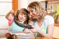 Child girl with mother cooking fish in the kitchen Royalty Free Stock Photo