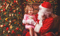 Child girl in nightgown sitting on lap of Santa Claus around Chr Royalty Free Stock Photo