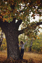 Child girl with old oak tree in autumn forest on the walk Stock Photo