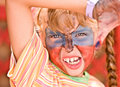 Child girl with paint on face in kids club. Stock Photo