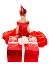 Child girl in party hat and red gift box. Royalty Free Stock Images