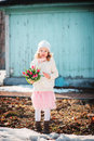 Child girl in pink skirt with bouquet of tulips having fun on the walk in early spring melting snow ground Royalty Free Stock Photo