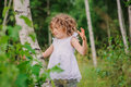 Child girl playing with birch tree in summer forest Royalty Free Stock Photo