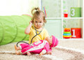 Child girl playing doctor with a doll kid in playroom Stock Images