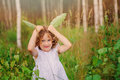 Child girl playing with green leaves in summer forest