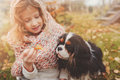 Child girl playing with her dog in autumn garden on the walk Royalty Free Stock Photo