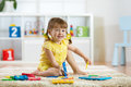 Child girl playing indoors with sorter toy sitting on soft carpet Royalty Free Stock Photo