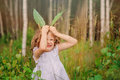 Child girl playing with leaves in summer forest with birch trees. Nature exploration with kids.