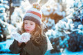 Child girl playing with snow in winter garden or forest, making snowballs and blowing snowflakes