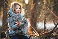 Child girl plays with pine cones on tree log in winter forest Royalty Free Stock Photo