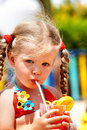 Child girl in  red bikini drink orange juice. Royalty Free Stock Photo