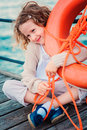 Child girl with rescue ring on wooden pier with sea background Royalty Free Stock Photo
