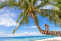 Child girl sitting on palm tree, tropical beach vacation Royalty Free Stock Photo