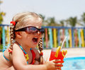 Child girl in sunglasses and red bikini drink. Stock Photography