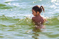 Child girl in water swimming and playing back view Royalty Free Stock Image