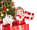 Child giving gift box by christmas tree. Royalty Free Stock Photo