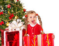Child giving gift box by christmas tree. Royalty Free Stock Image