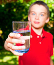 Child with glass of water boy holding outdoors focus on Stock Photo