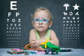 Child with glasses sits at a table on the background of the table for an eye examination and toys Royalty Free Stock Photography