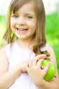 Child with green apple cute little girl is holding and smile outdoors Royalty Free Stock Images