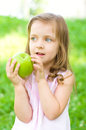 Child with green apple cute little girl is holding and smile outdoors Stock Photography
