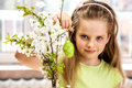Child hang easter egg on cherry branch indoor Stock Photos