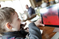Child has eclair and looking at tablet pc in the cafe Stock Image