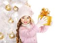 Child in hat and mittens holding christmas gift box gold near white tree isolated Royalty Free Stock Image