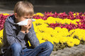 Child having allergy. Boy sitting outdoor with tissue near flowers Royalty Free Stock Photo