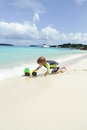 Child having fun on tropical beach near ocean toddler playing with toys a white sand caribbean Royalty Free Stock Image
