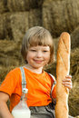 Child on haystack with bread and milk a Royalty Free Stock Photography