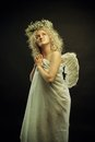 Child of heaven pretty angel with wings posing over dark background Royalty Free Stock Photography