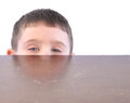 Child hiding behind kitchen table a little boy is a wooden and peaking out on a white background Stock Image
