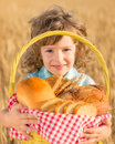 Child holding bread in basket happy with yellow autumn wheat field Royalty Free Stock Photos