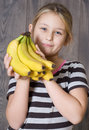 Child holding a bunch of bananas on wooden boards background Royalty Free Stock Image