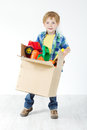 Child holding cardboard box packed with toys Royalty Free Stock Photo