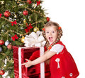 Child holding gift box by christmas tree. Royalty Free Stock Image
