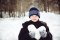 Child holding heart shaped snow in winter park. Royalty Free Stock Photography