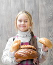 Child holding a lot of loaves smiling Stock Photos
