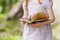 Child holding Open book and a bouquet of lilac Royalty Free Stock Photo