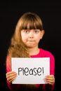 Child holding please sign studio shot of a made of white paper with handwriting Royalty Free Stock Image