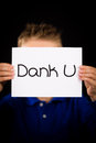 Child holding sign with dutch words dank u thank you studio shot of a Stock Image