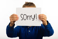 Child holding sorry sign studio shot of a made of white paper with handwriting Royalty Free Stock Photos
