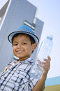 Child holding a water bottle holds of with buildings in the background Royalty Free Stock Photo