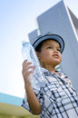 Child holding a water bottle holds of with buildings in the background Stock Photography